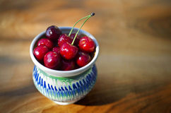 Ripe cherries in a rustic recipient. Ripe cherries in a rustic recipient on a wooden surface Stock Images