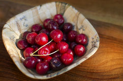 Ripe cherries in a rustic recipient. Ripe cherries in a rustic recipient on a wooden surface Stock Photos