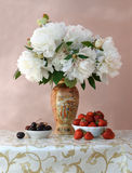 Ripe cherries and strawberries with bouquet of peonies royalty free stock photography