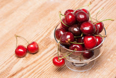 Ripe cherries in a transparent bowl. On wooden table Royalty Free Stock Image