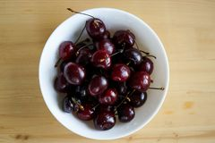 Ripe cherries  in a white deep plate. Juicy ripe cherries with water drops in a white deep plate on a light wooden background royalty free stock image