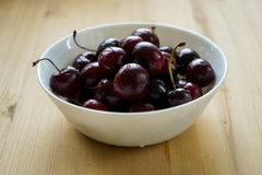 Ripe cherries  in a white deep plate. Juicy ripe cherries with water drops in a white deep plate on a light wooden background stock images
