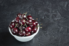 Ripe cherries in white plate. Ripe cherry berries in white plate on concrete background Royalty Free Stock Image