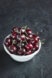 Ripe cherries in a white plate on a dark background. Ripe cherry berries in white plate on concrete background Royalty Free Stock Images