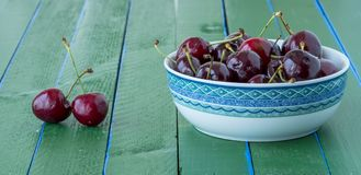 Some ripe cherries on a wooden green table. Stock Photo