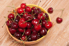 Ripe cherries in a yellow bowl, top view Royalty Free Stock Images