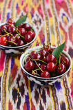 Ripe cherry in aian bowls on bright ethnic fabric Royalty Free Stock Image