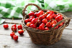 Ripe cherry. In basket on grey wooden background Stock Photo