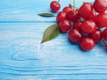 Ripe cherry berry on a blue wooden background, frame. Ripe cherry berry on a blue wooden background frame Stock Photo