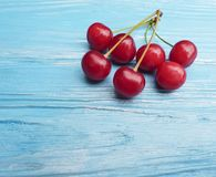 Ripe cherry berry healthy tasty vitamin delicious on a blue wooden background, summer frame. Ripe cherry berry on a blue wooden background frame summer healthy Stock Images