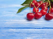 Ripe cherry berry healthy delicious on a blue wooden background, summer frame. Ripe cherry berry on a blue wooden background frame summer healthy delicious Stock Images