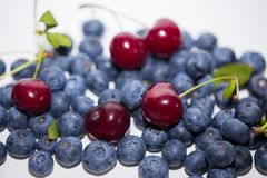 Ripe cherry with blueberries on a white background. Close-up of berries with selective focus stock photo
