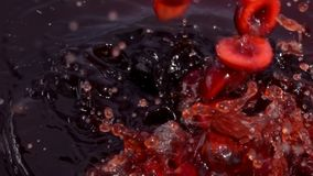 Ripe cherry fall into juice. With beautiful splashes in slow motion stock video footage