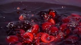 Ripe cherry fall into juice. With beautiful splashes in slow motion stock footage