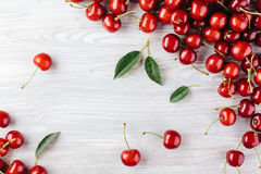 Ripe cherry with leaves on a wooden board. View from above Stock Photography