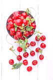 Ripe cherry in metal bowl. On a white wooden background royalty free stock photo