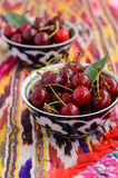Ripe cherry in oriental bowls on bright ethnic fabric Stock Photos