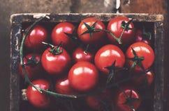Ripe cherry tomato branch in wooden box Stock Photo