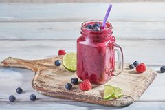 Fresh smoothie in a glass jar with ripe raspberries, blueberries and lime on rustic cutting board stock photography
