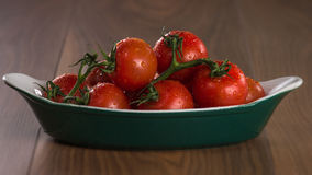 Ripe cherry tomatoes in a bowl on a wooden table. Ripe cherry tomatoes in a bowl on a wooden table royalty free stock photos