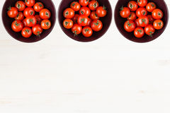 Ripe cherry tomatoes in purple bowl on white wood board with empty copy space as decorative border background. Stock Photos