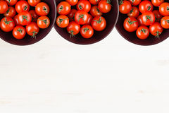 Ripe cherry tomatoes in purple bowl on white wood board with empty copy space as decorative border background. Stock Photo