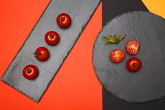 Ripe cherry tomatoes and rosemary composed on black slate boards on colorful background.  stock image