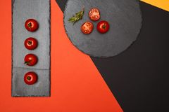 Ripe cherry tomatoes and rosemary composed on black slate boards on colorful background.  stock photography