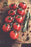 Ripe cherry tomatoes on rustic cutting board Royalty Free Stock Photos