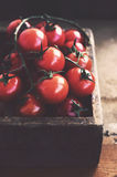 Ripe cherry tomatoes in rustic wooden crate Stock Photo