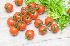 Ripe cherry tomatoes and salad frieze on a wooden table Royalty Free Stock Photos