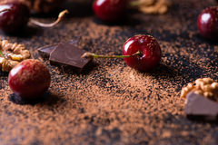 Ripe cherry, walnuts and chocolate chunks. Ripe cherry, cocoa powder, walnuts, and chocolate chunks on dark background, selective focus Royalty Free Stock Images