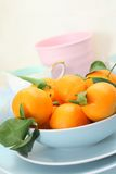 Ripe clementines on the blue, pastel plate Royalty Free Stock Photo