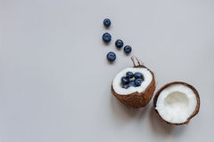 Ripe coconut with blueberry on the gray background, top view, with copy space Stock Photo