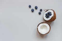 Ripe coconut with blueberry on the gray background, top view, with copy space Stock Images