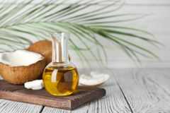 Coconut and oil in bottle on wooden table. Healthy cooking stock photography