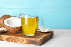 Ripe coconut and oil in pitcher on table. Healthy cooking Stock Photo