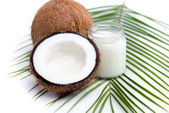 Ripe coconuts and organic coconut oil in glass jar on coconut leaf Stock Photos