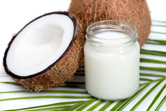 Ripe coconuts and organic coconut oil in glass jar on coconut leaf Stock Photography