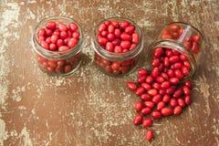 Ripe cornelian cherry in glass jars Stock Photography