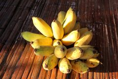 Ripe cultivated bananas. On woven wood table stock photos
