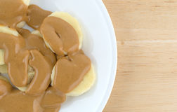 Ripe cut bananas covered with peanut butter on plate Stock Image