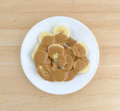 Ripe cut bananas covered with peanut butter on plate Royalty Free Stock Photography