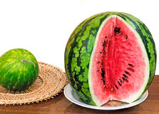The ripe cut water-melon on a white background. On a table surface on a dish the cut water-melon is located. It is presented on a white background Royalty Free Stock Image