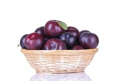 ripe delicious plums in a wicker basket on a white isolated background royalty free stock photography