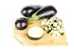 Ripe eggplant with cube cuts and slices on wood on Royalty Free Stock Photos