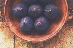 Ripe fall figs in clay dish on rusted metal background Royalty Free Stock Photography