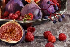 Ripe figs and berries in the silver plate. Ripe figs surrounded by berries Stock Images