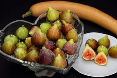 Ripe figs in a bowl on dark background. With a pumpkin. Some whole figs and one sliced in a white plate stock photo
