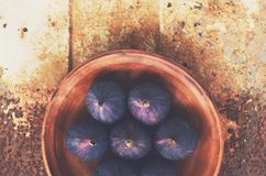 Ripe figs in clay bowl on rusted metal background Stock Image